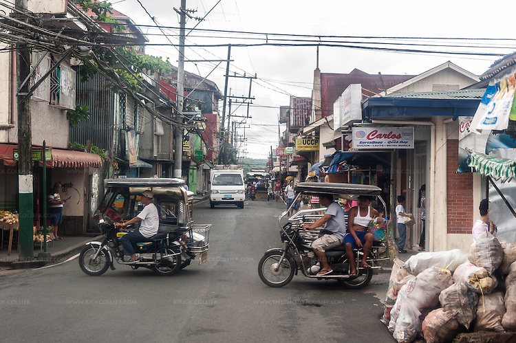 "Tricycles for hire dart across the street in front of ""my"" jeepney to Sampaloc on a misty early morning in Lucban, Quezon Province, the Philippines."