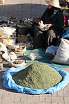 A woman prepares spices to sale in the Souk in Marrakesh, Morocco.