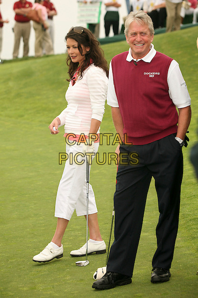 CATHERINE ZETA-JONES & MICHAEL DOUGLAS .9th Annual Michael Douglas & Friends Celebrity Golf Event at the Trump National Golf Club, Rancho Palos Verdes, California, USA..sport full length white pink striped stripes top cropped beige trousers married husband wife couple black beige vest sleeveless jumper hand in pocket.CAP/ADM/BP.©Byron Purvis/AdMedia/Capital Pictures