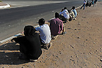 African asylum-seekers sit by a road as they wait for an occasional employer to give them work, in Eilat, southern Israel. The city, located close to Israel-Egypt border, hosts the largest amount of African asylum-seekers per capita in Israel.