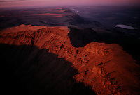 Blazing sunset leaves in shadow the famous gap in Kiger Gorge, atop Oregon's Steens Mountain. Bulldozing down to basalt, Ice Age glaciers carved our huge gorges out of the Great Basin's largest fault block mountain. Beyond, Steens's east face plummets a vertcal mile to the Alvord Desert.  The remote high desert region of southeast Oregon is protected under the Steens Mountain Cooperative Management and Protection Act of 2000.