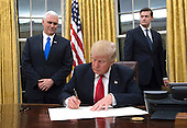 United States President Donald Trump signs a confirmation for Defense Secretary James Mattis in the Oval Office, at the White House in Washington, D.C. on January 20, 2017.     <br /> Credit: Kevin Dietsch / Pool via CNP