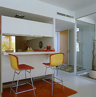 A pair of metal-framed colourful bar stools are pulled up to the breakfast counter of this compact contemporary kitchen
