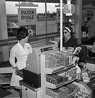 cliente et caissiere dans une epicerie<br /> ,28 mai 1966.<br /> <br /> On remarque les etalages de barres de chocolats et autres friandises.<br /> <br /> <br /> PHOTO :  Agence Quebec Presse - Photo Moderne
