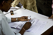 A government official is seen checking and matching the names of the voter ID holders before they cast their votes in a polling booth in Asia School, Bodakdev area of Ahmedabad, Gujarat India. About 49 per cent of the 3.65 crore electorate today exercised their franchise in the single phase polling in the state's 26 Lok Sabha constituencies on April 30th 2009.