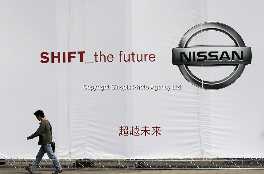 A man walks under an advertisement for Nissan in Shanghai, China..