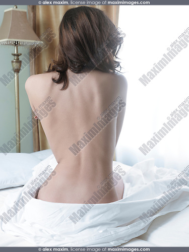 Back of a nude young woman sitting on a bed in front of a brightly lit window