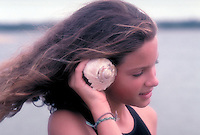She sells seashells - young girl listens to the ocean through a seahell. Girl at the beach.