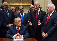 United States President Donald Trump listens as Governor Rick Scott (Republican of Florida) speak after signing S. 544 the Veterans Choice Program Extension and Improvement Act in the Roosevelt Room at the White House in Washington, DC on April 19, 2017. Photo Credit: Molly Riley/CNP/AdMedia