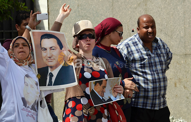 Supporters of Egypt's former president Hosni Mubarak, hold his pictures after his verdict hearing in a retrial for embezzlement outside the Maadi military hospital, on May 9, 2015 in the capital Cairo. The Egyptian court sentenced Mubarak and his two sons to three years in prison. Photo by Amr Sayed