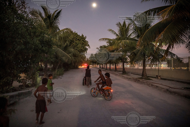 People on the only road that connects many islets of the atoll, but during extreme weather events and 'King Tides' it gets flooded by the sea.