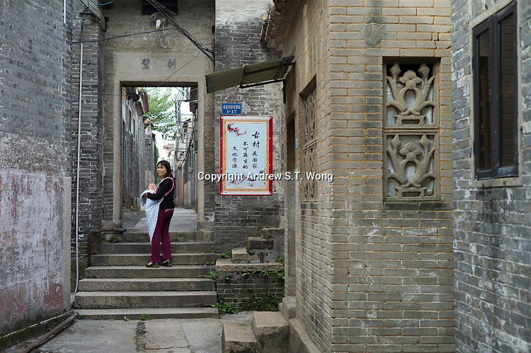 A woman carries a baby at the ancient Huangxi village in Dali of Nanhai district in Foshan city, Guangdong province, November 11, 2011.
