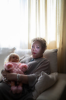 "Spain - Catarroja - Portrait of Práxedes Maxía Piqueras , 56. Práxedes Maxía Piqueras, 56, weeps uncontrollably while caressing the doll she had made for her daughter Jessica. ""I still have a little dress I had sewn for my baby"", she adds, gulping down some tranquillisers to compose herself. ""To come back from the hospital alone was the toughest thing I had to endure"". Jessica was born on the 23rd of August 1982 at the Hospital Sanjurjo, in Valencia. She supposedly died ten hours later because of several malformations, and was buried in a municipal common grave.  ""According to the medical reports my daughter was a monster, but when I held her on my lap she was perfectly fine!"", continues Maxía Piqueras, with a desperate voice. ""She had marvellous blue eyes and hair so blonde as if they had been dyed in saffron"". In 2013, Maxía Piqueras camped for 68 days in front of Valencia's main square, enchained, in order to press the authorities for the exhumation of her supposed daughter. Her case was dismissed a few weeks later."