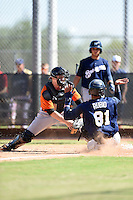 San Francisco Giants catcher Adam Sonabend (77) tags Elvis Rubio (81) sliding into home during an Instructional League game against the Milwaukee Brewers on October 10, 2014 at Maryvale Baseball Park Training Complex in Phoenix, Arizona.  (Mike Janes/Four Seam Images)