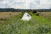 Electricity pylons cross marshland on the Kent shore of the Thames estuary.
