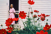 Farm lady at back door with flowers
