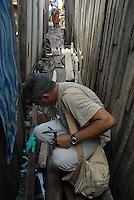 Técnicos da secretaria de saúde do estado do Pará, fazem fiscalização entrando em todas ás áreas de risco, o fiscal põe a bandeira amarela aviso de seu trabalho no bairro da Terra Firme ao lado do igarapé do Tucunduba, grande área de baixada onde moradores moram em favelas acima dágua. Confirmado o número de notificações em 4652 casos sendo 32 de dengue hemorrágica com 8 óbitos, diz ainda que pesquisas apontam que para cada caso notificado existem 20 sem o conhecimento da saúde pública. As principais instituições envolvidas na dateção e controle da doença  são o Instituto Evandro Chagas que faz a confirmação do diagnóstico , a secretaria do estado de saúde e o hospital Barros Barreto.<br /> Belé, Pará, Brasil.<br /> 27/04/2007<br /> Foto Paulo Santos/Interfoto