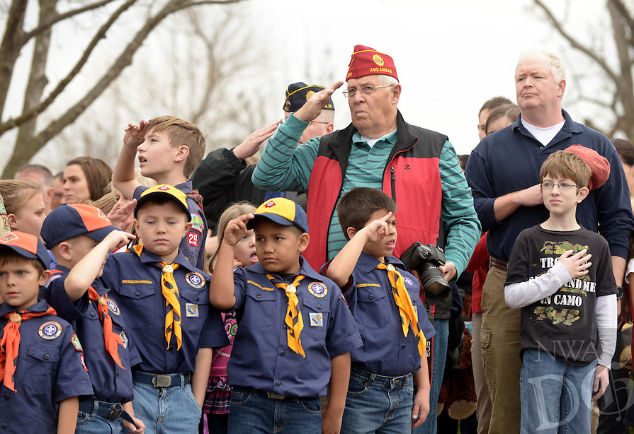 NWA Democrat-Gazette/BEN GOFF @NWABENGOFF<br /> Guests salute during the National Anthem on Saturday Dec. 12, 2015 during the Wreaths Across America ceremony at Fayetteville National Cemetery. Family members and volunteers with various veterans and community groups helped place a balsam remembrance wreath on the grave of each veteran at the cemetery as part of National Wreaths Across America Day.