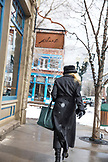 USA, Colorado, Aspen, a woman woman dressed in black shops her way through downtown Aspen