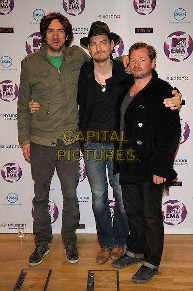Snow Patrol - Gary Lightbody, Paul Wilson and Jonny Quinn.2011 MTV European Music Awards EMA press briefing and photocall, Odyssey Arena, Belfast, Northern Ireland..5th November 2011.full length jeans denim green black jacket hat arm over shoulder .CAP/PL.©Phil Loftus/Capital Pictures.