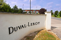 A sign at the gate in black letters on a white wall saying Duval-Leroy, with the winery in the background Champagne Duval Leroy, Vertus, Cotes des Blancs, Champagne, Marne, Ardennes, France
