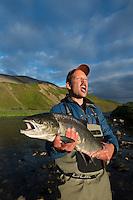 Mann med mellomlaks tatt en sommernatt, langt oppe i Komagelva. ---- Man holding salmon in Komagelva.