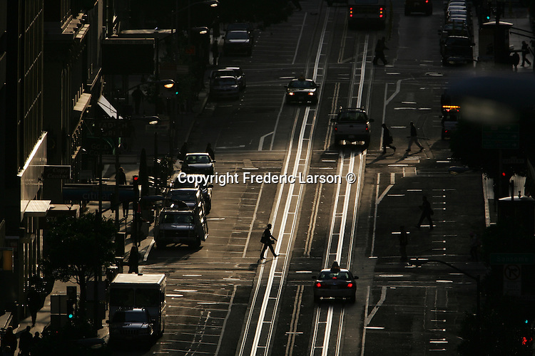 Early morning commuters cross California Street in San Francisco, California.