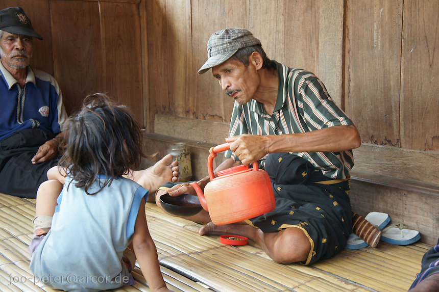 man pours water into coconut-cup for a child invillage Bena, Ngada people, Flores, Indonesia