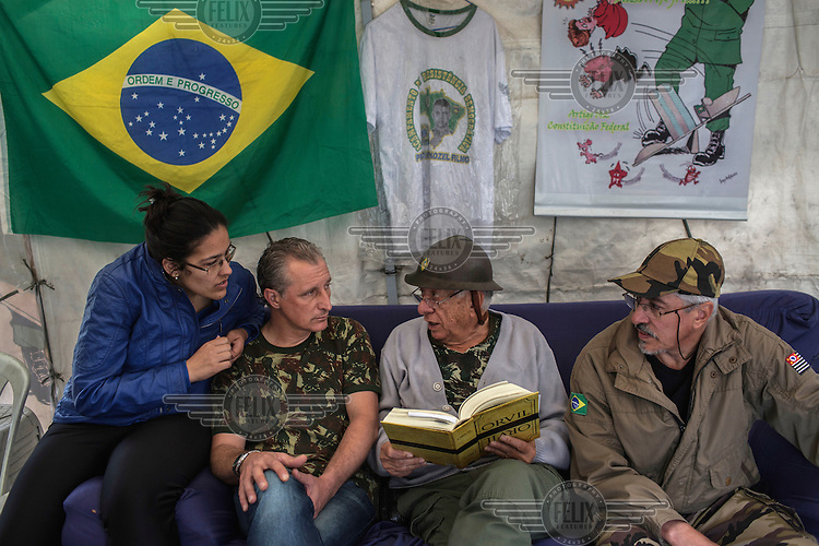 Retired sheriff Alberto Augusto, 72, centre, reads a book, called Orvil (which is book spelled backwards in Portuguese), with his son, Alberto Augusto Filho, 60, (right), Joyce Torres, 22, (left) and Sergio Veber, 51, (centre left), all members of the of the Brazilian Interventionist Resistence Movement (MBRI) at their headquarters, called PR 1 -Sergeant Mario Kozel Filho Military Interventionist Camp, a radical group that wants military intervention in the government.<br /> Their headquarters is a makeshift camp of tarps situated on an island in the middle of Sargeant Mario Kozel Filho Avenue, between the State Legislative Assembly and the Ministry of the Military, in Sao Paulo.<br /> <br /> After the end of the military dictatorship (1 April, 1964 to 15 March, 1985), a military commission produced a report on the events that occurred between 1964 and 1985 during the military's armed conflict with the left. It was developed in secrecy over three years and completed in 1988.