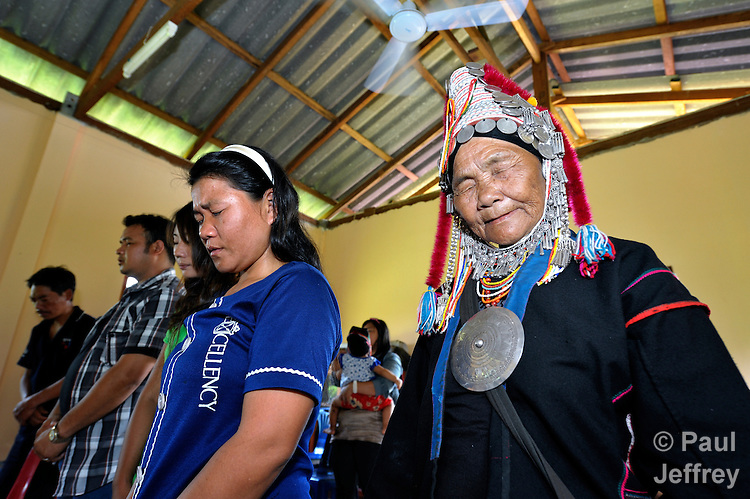 A traditionally dressed woman prays in the Pranetta United Methodist Church in Buyer, a small village in northern Thailand populated by indigenous hill tribe people.
