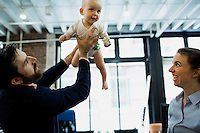 Dulcie Madden (right), co-founder and CEO of Mimo, and Mike Gutner, who handles operations at Mimo, play with 10-month-old Sadie Gutner at the Mimo headquarters Boston, Massachusetts, USA, on Mon., April 28, 2014. Sadie, daughter of Mike Gutner, is wearing one of the company's onesies, made by Mimo, which has a variety of sensors on it. The onesie has a detachable frog-shaped communication device that transmits data from the onesie's sensors and sends the data to a smartphone app, which displays information about the baby's respiration, skin temperature, position, and activity level. The onesie is washable and the device is water-resistant.