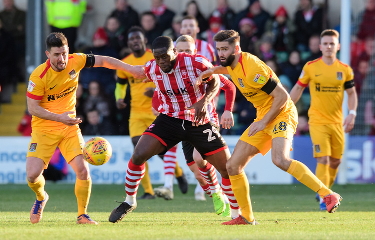 Lincoln City's John Akinde vies for possession with Northampton Town's David Buchanan, left, and Northampton Town's Jordan Turnbull<br /> <br /> Photographer Chris Vaughan/CameraSport<br /> <br /> The EFL Sky Bet League Two - Lincoln City v Northampton Town - Saturday 9th February 2019 - Sincil Bank - Lincoln<br /> <br /> World Copyright © 2019 CameraSport. All rights reserved. 43 Linden Ave. Countesthorpe. Leicester. England. LE8 5PG - Tel: +44 (0) 116 277 4147 - admin@camerasport.com - www.camerasport.com