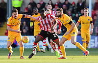 Lincoln City's John Akinde vies for possession with Northampton Town's David Buchanan, left, and Northampton Town's Jordan Turnbull<br /> <br /> Photographer Chris Vaughan/CameraSport<br /> <br /> The EFL Sky Bet League Two - Lincoln City v Northampton Town - Saturday 9th February 2019 - Sincil Bank - Lincoln<br /> <br /> World Copyright &copy; 2019 CameraSport. All rights reserved. 43 Linden Ave. Countesthorpe. Leicester. England. LE8 5PG - Tel: +44 (0) 116 277 4147 - admin@camerasport.com - www.camerasport.com