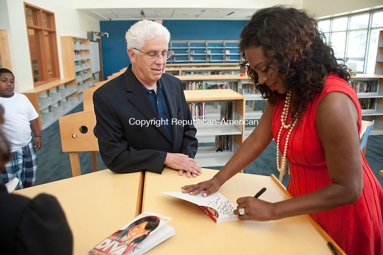 """WATERBURY, CT-03 AUGUST 2012--08032JS09-Waterbury native and actress Sheryl Lee Ralph, right, signs a copy of her book """"Redefining Diva : Life Lessons from the Original Dreamgirl"""" for Waterbury Board of Education President Charles Stango during a visit to the new Jonathan E. Reed School Friday.  During the visit, Ralph was awarded with the Key to the City by Waterbury Mayor Neil M. O'Leary. Stango told Ralph, when he was a student at Tinker School in the 1950's, his music teacher was her father Dr. Stanley Ralph..Jim Shannon Republican-American"""