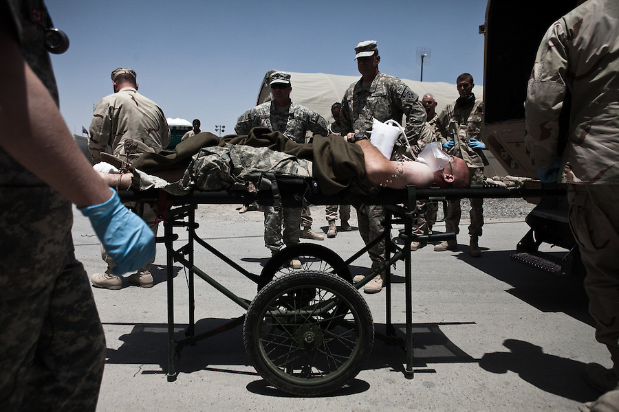 "A soldier whose lower leg has been severely damaged by a RPG in Kandahar's Zhari Province is unloaded from an ambulance at the military hospital at Kandahar Airfield. Scenes from the medical evacuations of wounded Americans, Canadians, and Afghan civilians and soldiers being flown by Charlie Co. 6th Battalion 101st Aviation Regiment of the 101st Airborne Division. Charlie Co. - which flies under the call-sign ""Shadow Dustoff"" - flies into rush the wounded to medical care out of bases scattered across Oruzgan, Kandahar, and Helmand Provinces in the Afghan south. These images were taken of missions flown out of Kandahar Airfield in Kandahar Province and Camp Dwyer in Helmand Province."