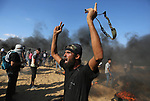 Palestinian protesters gather during clashes with Israeli troops in tents protest where Palestinian demand the right to return to their homeland at the Israel-Gaza border, in Khan Younis, in the southern Gaza Strip on July 20, 2018. Photo by Ashraf Amra