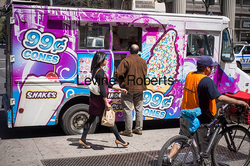 Frugal ice cream lovers enjoy a frosty treat from 99 cent cones soft ice cream truck in the East Village neighborhood in New York on Wednesday, May 1, 2013. (© Richard B. Levine)