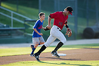 A young baseball player takes the field with Kannapolis Intimidators shortstop Grant Massey (28) prior to the game against the Hagerstown Suns at Kannapolis Intimidators Stadium on June 15, 2017 in Kannapolis, North Carolina.  The Intimidators defeated the Suns 9-1 in game two of a double-header.  (Brian Westerholt/Four Seam Images)
