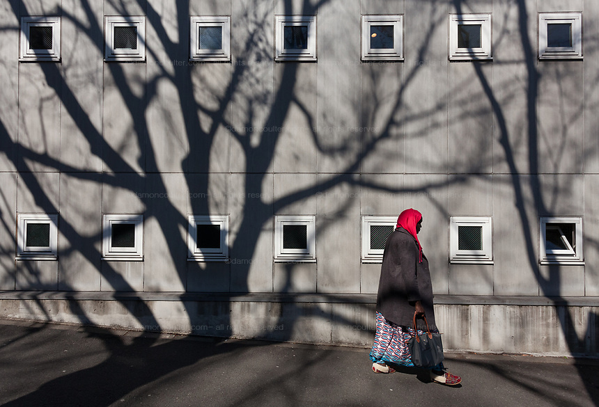 A Muslim woman in a red hijab walk by a wall with windows and tree shadows near the Tokyo Camii mosque in Yoyogi-Uehara, Tokyo, Japan. Friday March 8th 2019. The Tokyo Camii Mosque is the largest mosque in Japan where estimate currently put the immigrant and native population of Muslims at around 130,000.