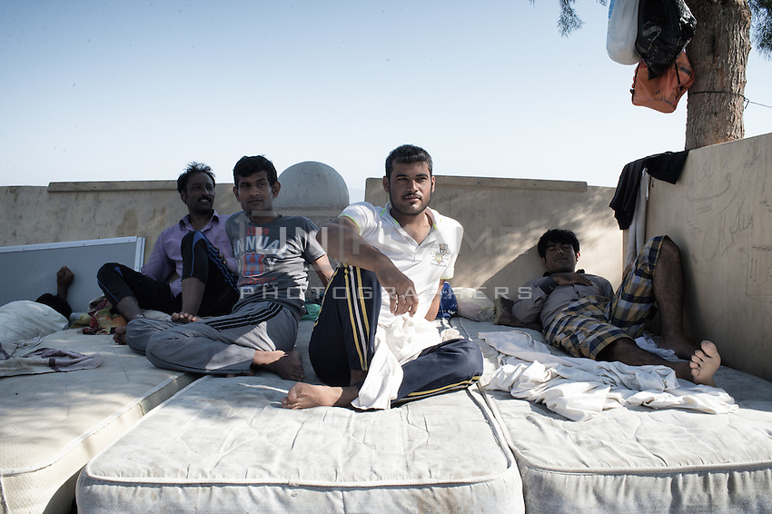 Group of Pakistani friends waiting for their papers, relaxing in a makeshift, roadside living room. Kos, Greece. Sept. 5, 2015