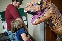 NWA Democrat-Gazette/CHARLIE KAIJO Joshua Debes of Ozark and Shaylea Debes, 6 of Springdale say hello to Nikolas Siler, 15 of Rogers dressed as a T-Rex on Sunday, November 12, 2017 at Four Points Sheraton Hotel in Bentonville. The Hotel hosted the Arkansas Anime Festival - Northwest Arkanas Edition 2017. Fans enjoyed product displays, gaming parties and artist Q&As