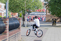 A boy cycles in a housing estate, ignoring the open top bus Homecoming of the Wales Euro 2016 Squad in Cardiff City Centre, Cardiff. 8 July 2016. Photo by Mark  Hawkins / PRiME Media Images.