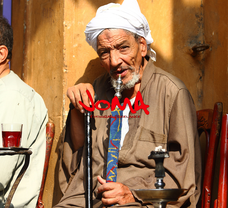 Older man taking a tea and smoking a sisha in the street