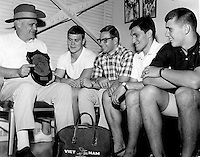 """""""Vietnam Report.""""  Wearing his prize possession, an Aussie hat, Woody Hayes displays a plaque he received from a U.S. Marine unit in Viet Nam to four young men who will be Ohio State freshmen footballers in the fall.  The plaque was given to Woody in appreciation of his visit with the Marines.  Left to right, the Buckeyes-to-be are Tom Backhus, Cincinnati; Dave Brungard, Youngstown; Bob Trapuzzano, McKey's Rock, Pa.; and Paul Huff, Dover.  (Columbus Dispatch photo)"""