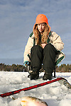A teenage girl ice fishes on a lake in northern Wisconsin.
