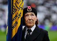 2nd November 2019; London Stadium, London, England; English Premier League Football, West Ham United versus Newcastle United; A female member of the Royal British Legion with the Union Jack Flag stands for a minute silence - Strictly Editorial Use Only. No use with unauthorized audio, video, data, fixture lists, club/league logos or 'live' services. Online in-match use limited to 120 images, no video emulation. No use in betting, games or single club/league/player publications