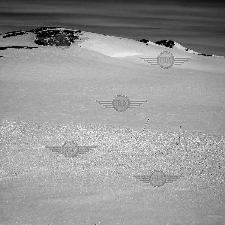 Two poles stick in the snow on a snow covered landscape in East Greenland, north of Mestersvig. Mestersvig is a military outpost with a runaway in the Scoresby Land region of the Northeast Greenland National Park. Originally built in anticipation of mining in the area it has been run by the Danish defence department since 1988. The place is staffed by two men whose duties include maintenance of buildings and the airfield and support of other activities in the area.