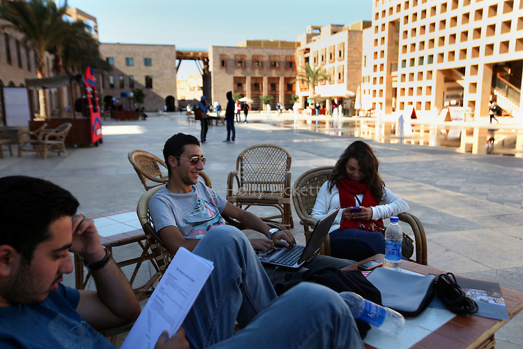 Left to right, Muhammad Nadim, 20, Ramy Asaad, 19, and Lamis Galal, 19, hang out on campus at the American University in Cairo, Egypt, Nov. 9, 2010. Nadim studies economics while Asaad and Galal study art and design. Cairo's most prestigious university costs around $10,000 per semester.
