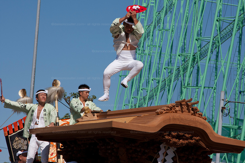 A man, called a daiku kata, jumps across the roof of a Danjiri float as it turns a corner during he Kishiwada danjiri matsuri, Kishiwada, Sunday September 20th 2009. Ornately carved floats called Danjiri are pulled through the streets of Kishiwada during the danjiri festival or matsuri. Each float weigh about 4 tonnes and stands over 3 metres high. They are pulled by teams of up to a thousand people, young and old, and each challenges itself to skid the danjiri round street corners at great speed.