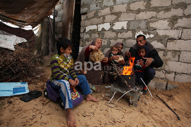 Palestinians warm themselves around a fire outside their dwellings in Khan Younis in the southern Gaza Strip December 19, 2016. Photo by Ashraf Amra